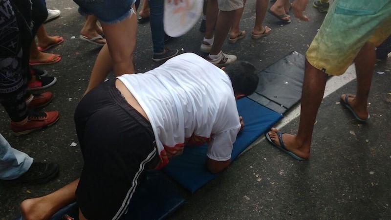 O promesseiro Carlos Bruno, 24 anos percorre o trajeto da procissão de joelhos, com a ajuda de amigos, na manhã deste domingo (8). Círio 2017 (Foto: Andréa França / G1)