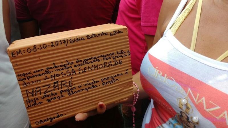 Promesseira carrega tijolo na procissão. (Foto: Luiz Fernandes/ G1)